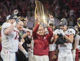 Alabama Crimson Tide head coach Nick Saban hoists the National Championship trophy