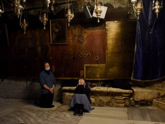 Nuns Pray In The Grotto Of The Church of Nativity On Christmas Eve