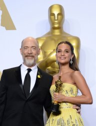 J. K. Simmons and Alicia Vikander, holding her award, backstage at the 88th Academy Awards in Hollywood