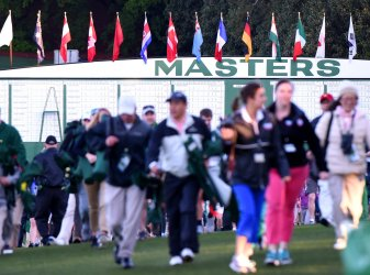 Fans arrives and walk quickly to the first tee box at the Masters