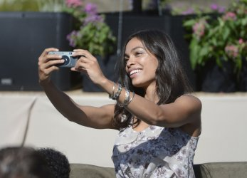 Rosario Dawson takes a picture while attending an address by President Barack Obama Keene, California