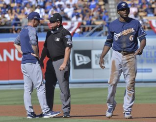 Brewers manager Counsell talks with umpire Gibson after Cain out at second in NLCS Game Five