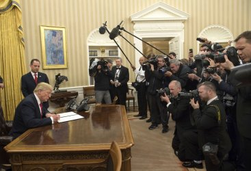 President Donald Trump signs his first executive order at the White House
