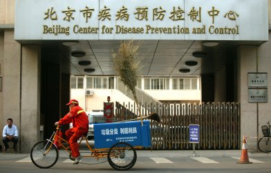 A Chinese street cleaner bicycles past hospital in Beijing