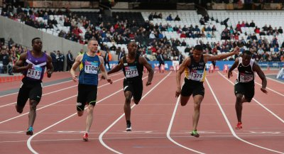 Athletes compete in the 100 metres in the Olympic stadium.