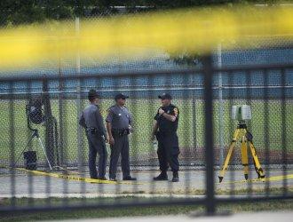 Law enforcement work the scene near Simpson field where a gunman opened fire in Alexandria, Va.