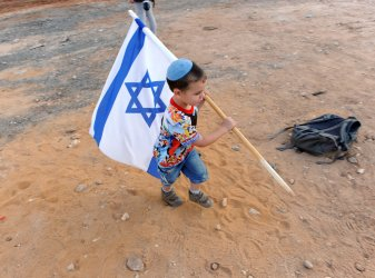 An Israeli settler boy  plays during a protest against the Palestinian bid for statehood near Hebron, West Bank