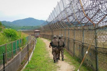 Soldiers walk beside a fence in the DMZ Peace Trail.