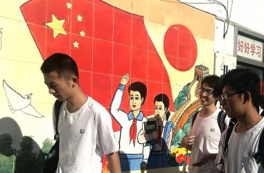 Chinese students walk past a government mural in Beijing, China