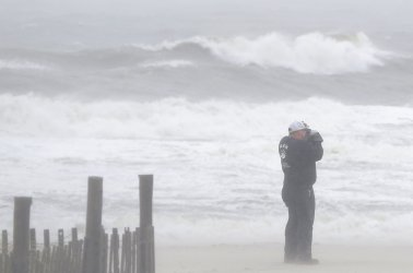 A man takes photos on the beach during stormy weather