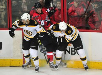 Capitals John Carlson fights for the puck with Bruins' Tyler Seguin and David Krejci in Washington