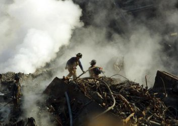 Smoke billows as firefighters continue to pour water on the simmering ruble at the site.