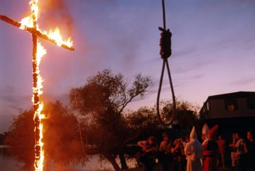 A burning cross and a noose are part of the festivities at a Ku Klux Klan rally.