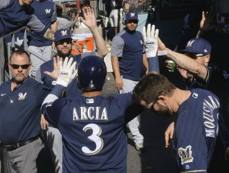 Brewers Arcia celebrates scoring with teammates in NLCS Game Five