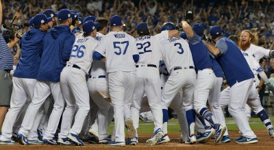 Dodgers Turner swarmed at home plate by his teammates in the NLCS