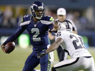 Seattle Seahawks' quarterback Josh Portis stiff arms Oakland Raiders' cornerback Pat Lee in Seattle.