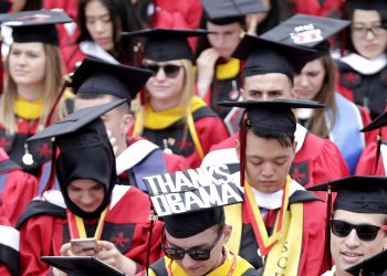 A graduate wears a graduation cap with message Thanks Obama