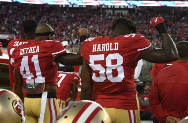 49ers Antoine Bethea and Eli Harold hold up clenched fist during the National Anthem