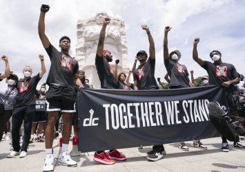 Members of the Washington Wizards and Mystics rally for Juneteenth at the Martin Luther King JR. Memorial