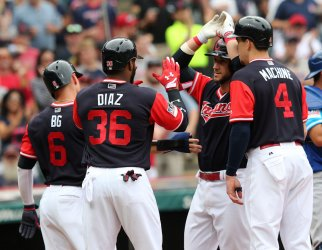 Indians Gomes is greeted at home plate after hitting a grand slam against the Royals