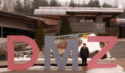 A tourist poses for a photo at a visitor center in the DMZ
