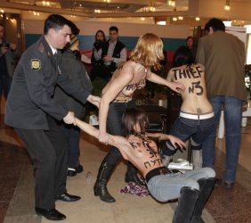 Police detain Ukrainian group Femen protesting at a polling station
