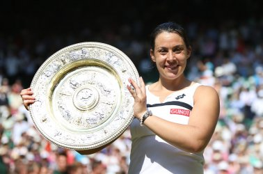 Marion Bartoli holds the Winners Trophy after victory in the Women's Final match against Sabine Lisicki
