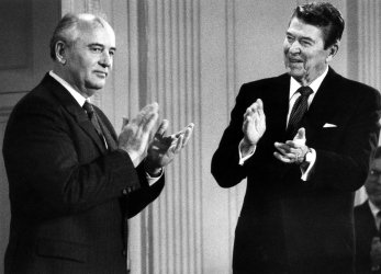 PRESIDENT REAGAN AND MIKHAIL GORBACHEV APPLAUD AFTER SIGNING ARMS TREATY