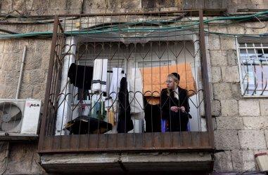 An Ultra-Orthodox Boy Sits On A Balcony In Jerusalem
