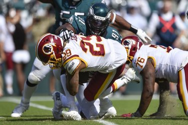 Redskins' Derrius Guice is tackled by Eagles' Fletcher Cox