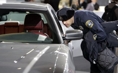 A Detroit police officer looks at the new Dodge Charger at the 2011 NAIAS in Detroit, MI.