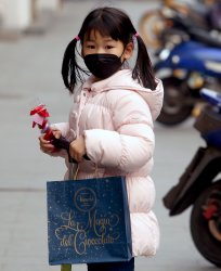 A Chinese girl wears a protective face mask outside a shop  in Beijing, China