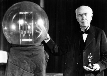 Thomas Edison seen here in 1929 holding a replica of his first lamp.