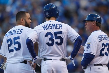Royals' Kendrys Morales and Eric Hosmer talk with Mike Jirschele during game 2 against the Astros