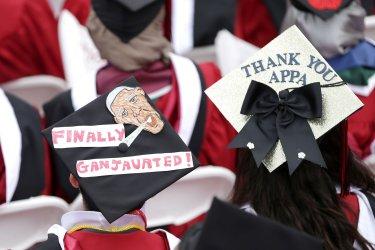 A Graduates wear graduation caps with Obama likeness