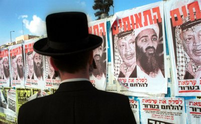 An Ultra-Orthodox Jews looks at posters of Osama Bin Laden and Palestinian leader Yasser Arafat in Jerusalem