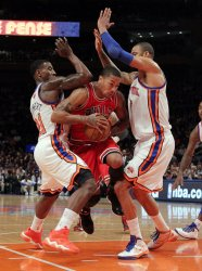 Chicago Bulls Derrick Rose drives the ball between New York Knicks Iman Shumpert and Tyson Chandler at Madison Square Garden in New York