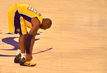 Lakers Kobe Bryant ties his shoe during game against the Spurs