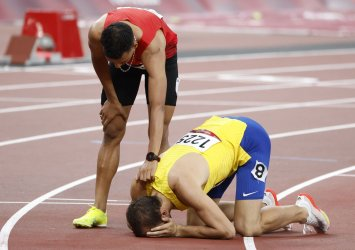 Morocco's Nabil comforts Bosnia and Herzegovina's Tuka after 800m semifinal in Tokyo, Japan