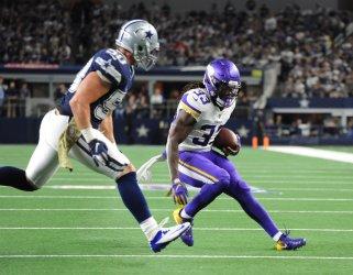 Vikings running back Dalvin Cook (33) runs against Cowboys defensive end Demarcus Lawrence