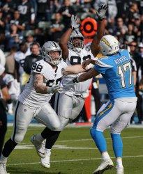 Oakland Raiders teammates Maxx Crosby(L) and P.J.Hall pressure Los Angeles Chargers quarterback Philip Rivers