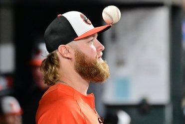 Orioles pitcher Andrew Cashner balances baseball on cap