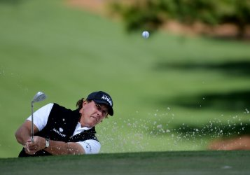 Phil Mickelson hits out of a bunker at the Masters