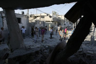 Palestinians inspects their houses after an Israeli military strike