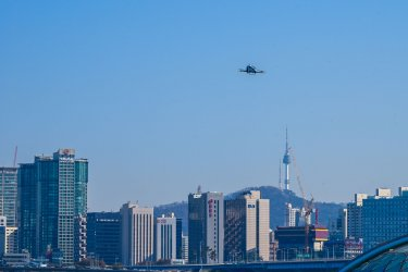 A Drone Taxi Flies in Front of Seoul Skyline