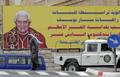 Palestinians walk past a billboard of Pope Benedict XVI in Bethlehem, West Bank