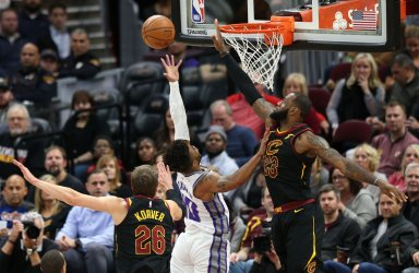 Sacramento Kings' Frank Mason III puts up a shot between Cleveland Cavalier defenders Kyle Korver (26) and LeBron James