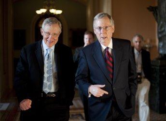 Senate Majority Leader Harry Reid and Senate Minority Leader Mitch McConnell walk together in Washington