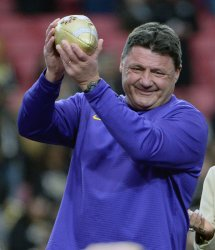 LSU's head coach Ed Orgeron holds trophy