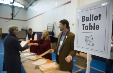 Poll workers hand out ballots to voters in Alexandria